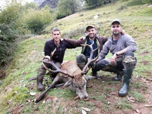 Venado abatido. Miguel, Julín y Paul, con el ejemplar cazado en la Panda, con disparo de Julín, en el coto de Aller. :: Román Ruea